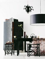 Oriental-style, dark wood stools at table below designer pendant lamp
