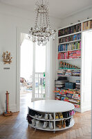Shoes stored on shelves of white, round, low table on herringbone parquet floor and chandelier in front of bookcase next to open door leading to living room