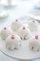 Mini cakes with white coating and marzipan roses on a porcelain dish