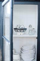 White crockery in open cupboard with glass door