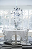 Designer pendant lamp above dining table and white chairs on black and white striped rug