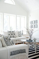 Pale, Scandinavian-style attic interior with comfortable sofa set and scatter cushions