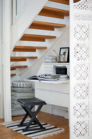 Workstation in niche below stairs - black stool on rug in front of white bureau