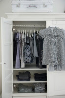 Dresses hanging in open wardrobe and girl's dresses hanging on door on coat hangers