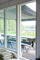 View through floor-to-ceiling windows and glass door of wooden deck with rustic table and benches below awning