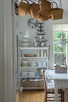 Corner of dining room with white dining set, baskets hanging from ceiling and white-painted, open-fronted shelves of crockery against wall