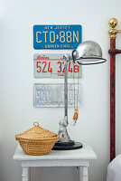 Retro table lamp and wicker basket with lid on vintage bedside table below American car number plates on wall