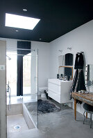 Loft-apartment bathroom with black-painted ceiling above sunken shower base in concrete floor and vintage console table as cosmetics station