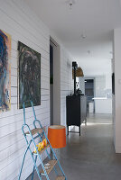 Stepladder below modern paintings on wood-clad wall and 70s lamp with orange lampshade