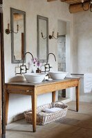 Twin wash basins on rustic wooden table and improvised wall-mounted taps below vintage-effect mirrors