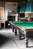 Pendant lamps with pleated fabric lampshades above snooker table in rustic interior