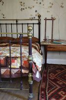 Brass-framed double bed and patterned rug in rustic setting