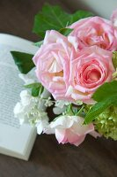 Bouquet of pale pink roses and open book on wooden surface