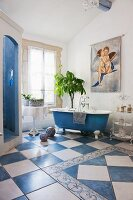 Bathroom with blue and white floor tiles, free-standing bathtub and separate shower area