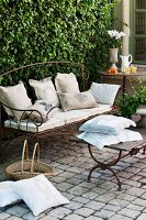 Wrought-iron garden bench with cushions on cobbled terrace seating area