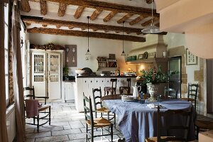 Rustic kitchen-dining room with wooden table; counter with bar stools in background