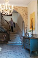 Wooden chest of drawers and chandelier in foyer with archway and staircase