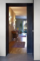 View of modern interior with traditional ambiance through open sliding door - runner on parquet floor and antique bureau