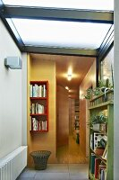 Foyer with frosted glass ceiling and view into hallway with warm artificial lighting