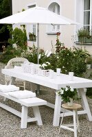 Wicker baskets and porcelain crockery on white picnic table in garden