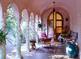 Antique and vases in a pink arcade with arched double doors