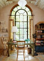 Old wooden table with a glass top in front of a large arched window in the attic with wooden beam ceiling