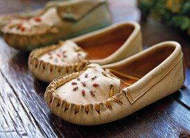 White children's moccasins with bead work on a dark wooden floor