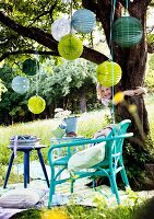 Patterned lanterns hanging from tree in garden