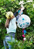Woman hanging rice paper lantern decorated with round stickers and pompoms in garden