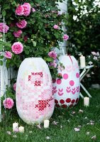 Large paper lanterns with embroidery-style patterns in garden