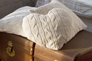 Various cushions with white knitted covers on old trunk