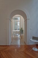 Classic arched doorway in foyer and view of round table in dining room with terrazzo floor