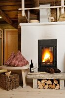 Cosy atmosphere with log fire in living room of renovated wooden hut