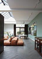 Rust-coloured floor cushions on dark herringbone floor in open-plan interior with skylight