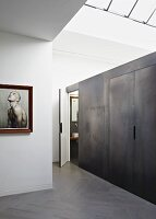 Installation with metal-effect wall in minimalist interior with skylight