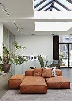 Various large, rust-coloured floor cushions in modern interior below skylight in ceiling