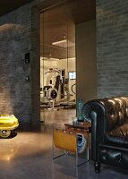 Black vintage leather armchair and magazine rack in front of brick wall with view of gym through glass door