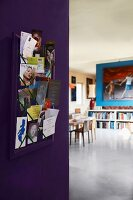 Photos and cards on pinboard on purple corridor wall with view into modern dining room beyond