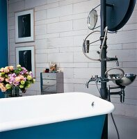 Modern, free-standing sculptural water installation with wash basin and bath taps next to vintage bathtub