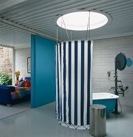 Blue and white striped awning fabric stretched between ceiling and floor around free-standing bathtub below circular skylight