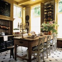 Rustic dining table with white wooden chairs in country house kitchen