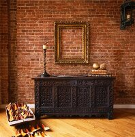 Carved wooden trunk against brick wall