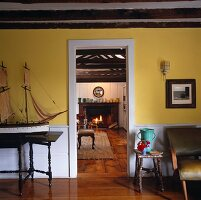Yellow-painted foyer with open doorway and view into country house living room with fireplace