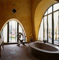 Masonry bathtub in bathroom of Mediterranean house with arched windows