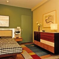 Wooden-fronted sideboard opposite bed against green-painted wall in bedroom