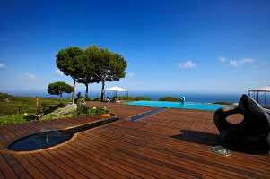 Spacious wooden terrace with water channel leading to infinity pool and sea view