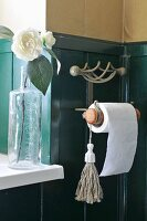 Corner of bathroom with half-height wood-panelling and toilet roll holder next to flower in vase on windowsill