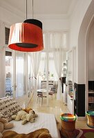 Soft toys on sofa, colourful stools and red and black pendant lamps in child's bedroom with open glass door leading to playroom in background