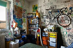 Bike hanging on graffitied wall above shelves in teenager's bedroom
