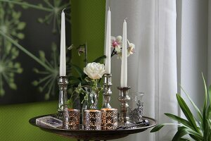 Silver candlesticks and tea light holders on tray